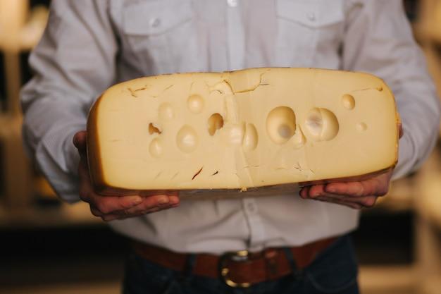 Feche acima do homem hansome mantenha grande fatia de queijo maasdam na mão. queijo com grandes buracos. fundo de prateleiras com queijo