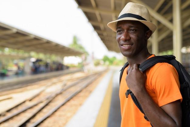 Feche acima do homem jovem turista feliz sorrindo e pensando enquanto aguarda o trem na estação ferroviária contra a vista dos trilhos do trem em bangkok tailândia