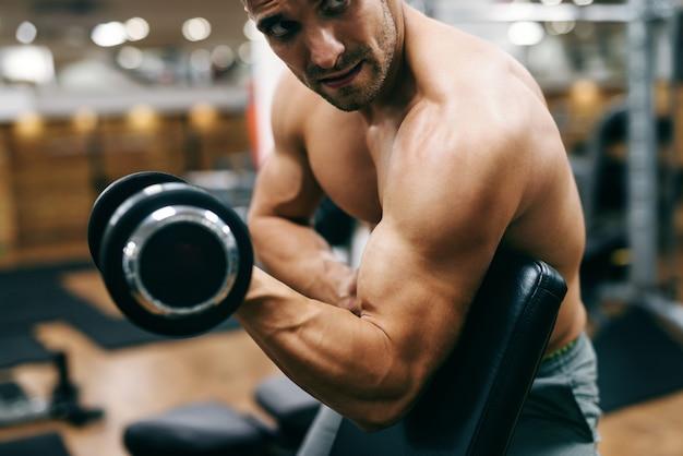 Feche acima do homem musculoso sem camisa, fazendo exercícios para bíceps com halteres
