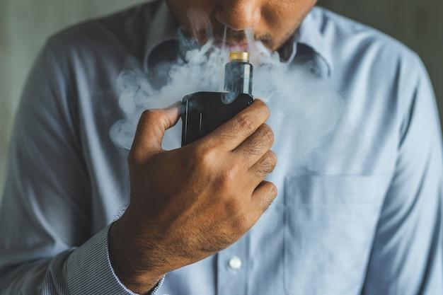 Feche acima do homem novo que fuma um cigarro eletrônico.