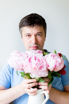 Feche acima do homem novo que guarda flores. homem em uma máscara médica antivírus detém um buquê de flores. recuperação de coronavírus. parar a pandemia de covid-19