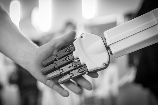 Feche acima do homem que agita as mãos com um robô