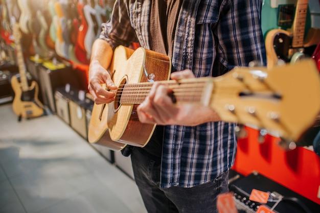 Feche acima do homem que está e que joga no violão. ele se veste como hipster. guy está sozinho no quarto.