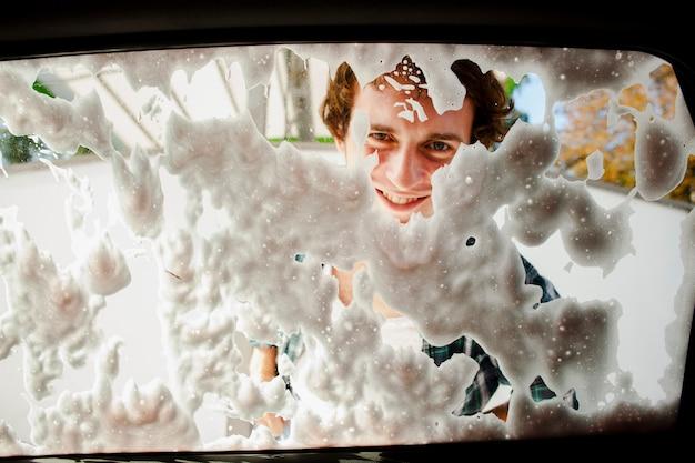 Feche acima do homem que lava a janela traseira