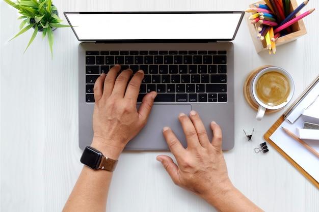 Feche acima do homem que trabalha no portátil ao sentar-se na mesa de madeira branca no escritório moderno.