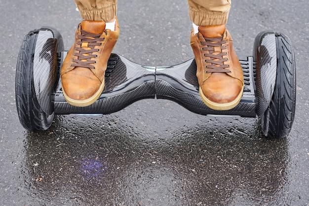 Feche acima do homem que usa o hoverboard na estrada asfaltada. pés na scooter elétrica ao ar livre