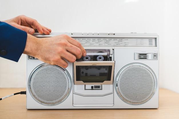 Feche acima do homem que usa um rádio velho dentro de casa.