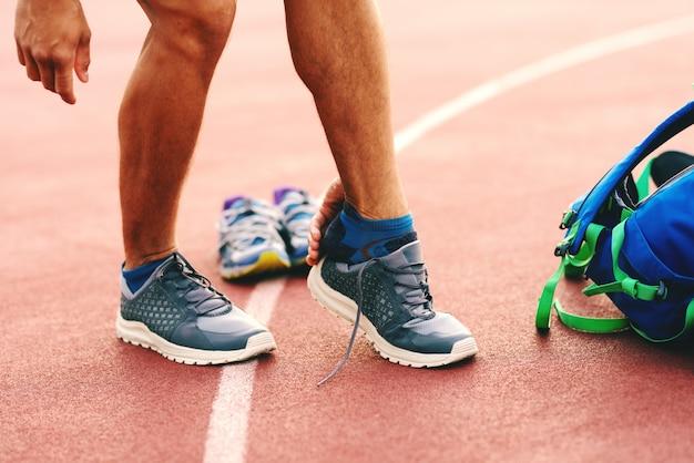 Feche acima do homem que veste a sapatilha antes de treinar.