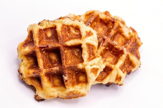 Feche acima do isolado da sobremesa dos waffles do caramelo no fundo branco.