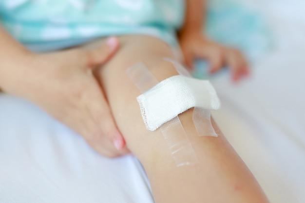 Feche acima do joelho da criança com um emplastro (para feridas), foco seletivo na atadura.