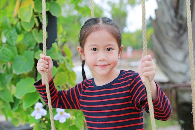 Feche acima do jogo asiático pequeno feliz da menina da criança e do assento no balanço no parque natural.