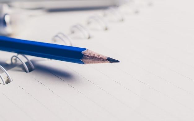 Feche acima do lápis azul no conceito do fundo da educação do caderno.