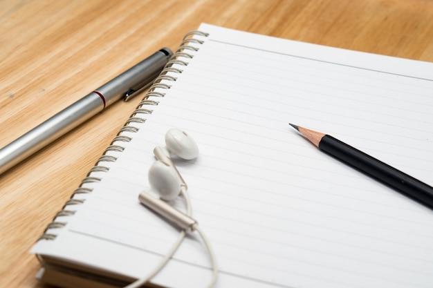 Feche acima do lápis, caneta de tinta, fone de ouvido e caderno em branco sobre fundo de madeira.