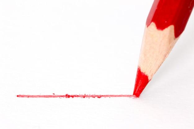 Feche acima do lápis vermelho com curso isolado no fundo branco