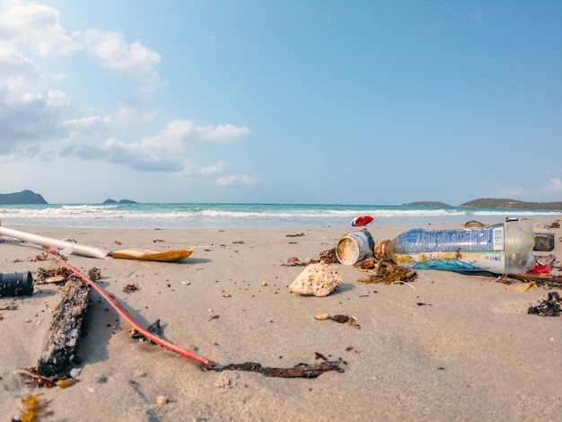 Feche acima do lixo de sucata sujo no fundo da poluição do ambiente da praia.