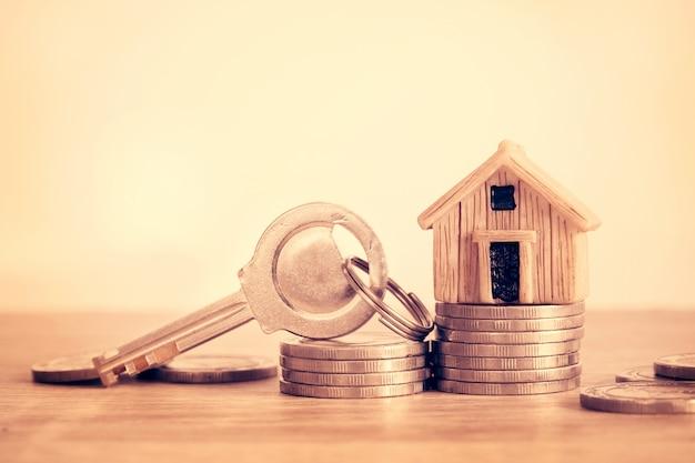Feche acima do lugar do modelo da casa no empilhamento da moeda do dinheiro para um conceito do hipoteca e do empréstimo, do refinance ou do investimento da propriedade