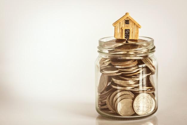 Feche acima do lugar do modelo da casa no empilhamento da moeda do dinheiro para uma hipoteca e um empréstimo de casa