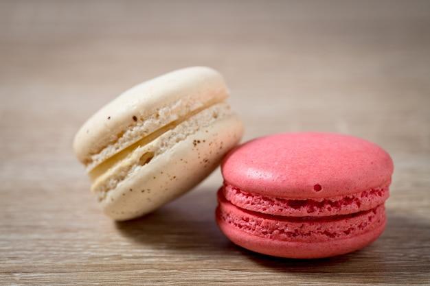 Feche acima do macaron do bolo ou macaroon no fundo de madeira, sobremesa doce