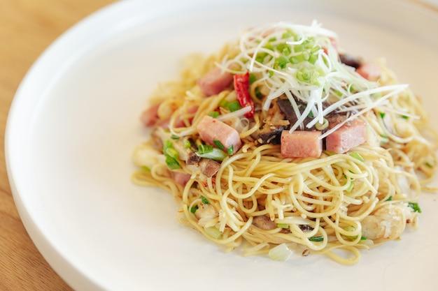Feche acima do macarrão chinês frito com presunto e carne de caranguejo no fundo da mesa de madeira