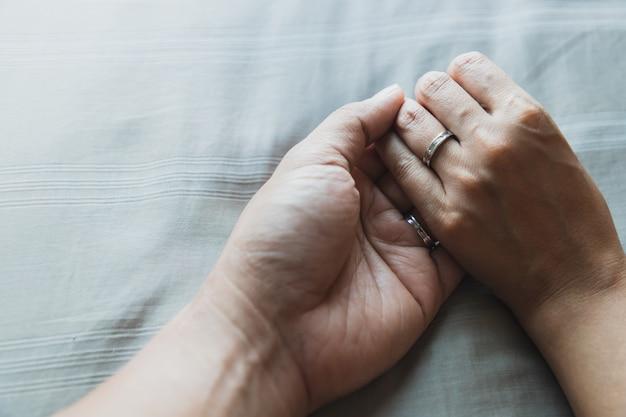 Feche acima do marido e esposa mãos juntos em camas cinzentas e anéis de casamento bonito