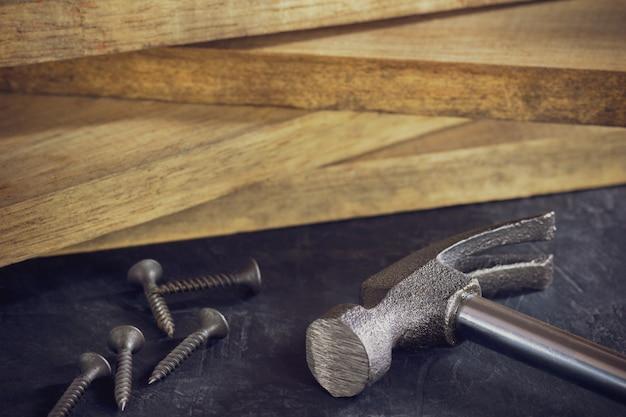 Feche acima do martelo e parafuse no empilhamento da madeira serrada. copie o espaço. conceito de carpinteiro ou construção.