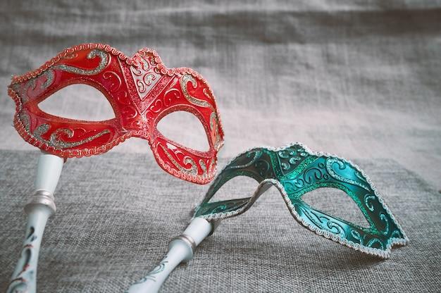 Feche acima do masquerade venetian vermelho e verde, lugar da máscara do carnaval no pano de saco de serapilheira