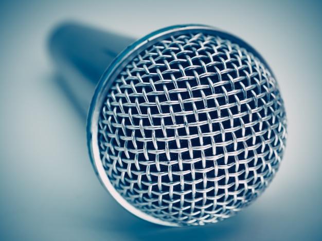 Feche acima do microfone para o quarto do karaoke ou a sala de conferências.