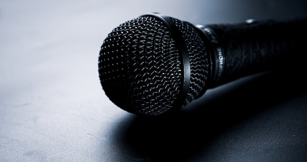 Feche acima do microfone preto em um fundo preto.
