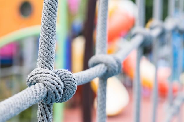 Feche acima do nó da corda em escalar redes no campo de jogos.