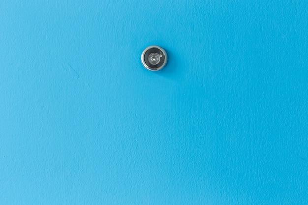Feche acima do olho mágico da lente de porta na textura de madeira azul