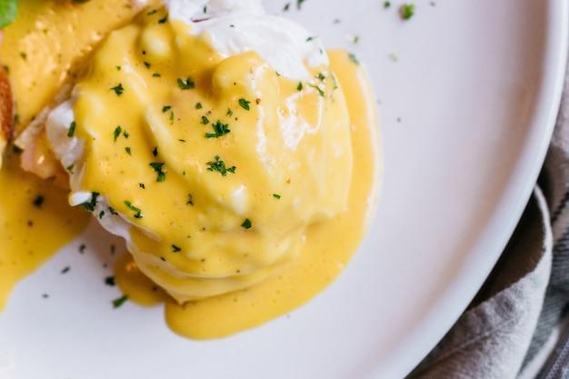 Feche acima do ovo benedict servido com salada na placa branca na tabela de madeira.