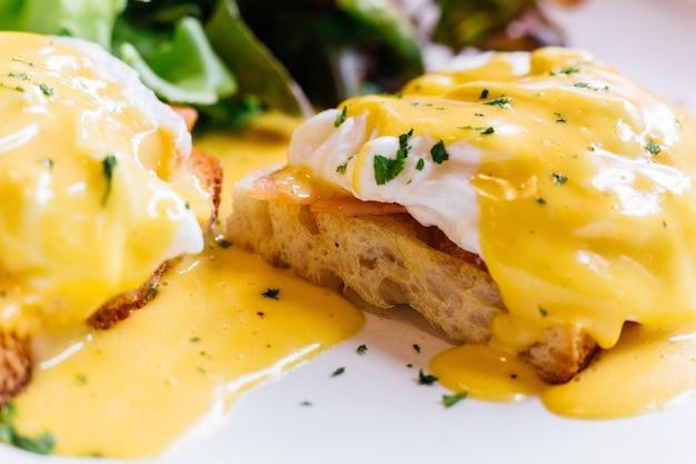 Feche acima do ovo benedict servido com salada na placa branca.
