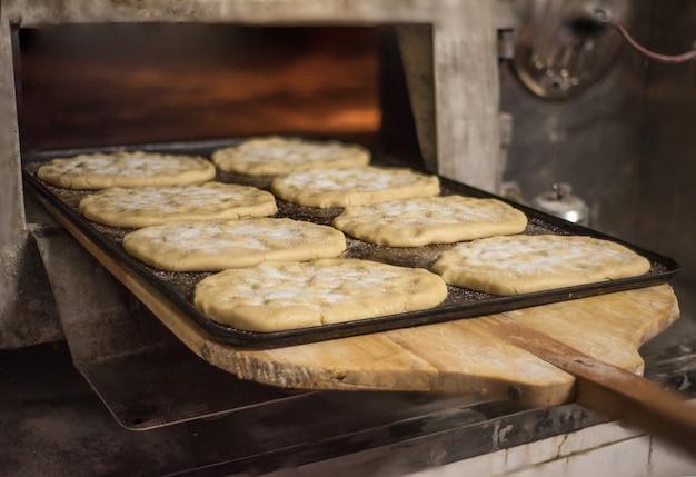 Feche acima do padeiro que põe na pastelaria fresca do forno.