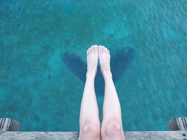 Feche acima do pé e do pé da mulher sobre o mar azul.