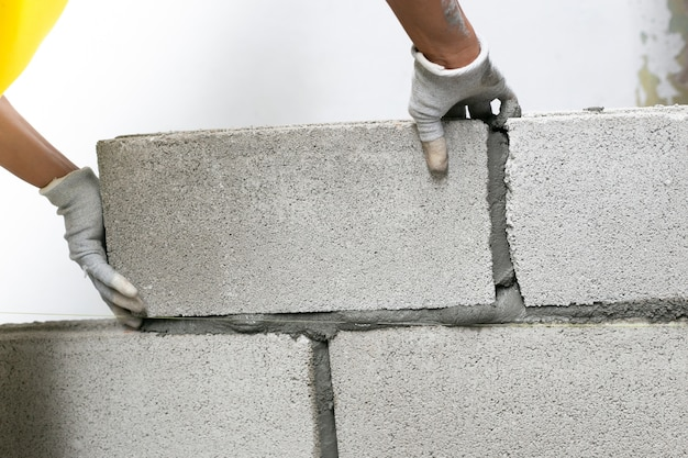 Feche acima do pedreiro industrial que instala tijolos no canteiro de obras, construindo paredes.