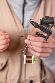 Feche acima do pescador que amarra uma mosca para pescar.