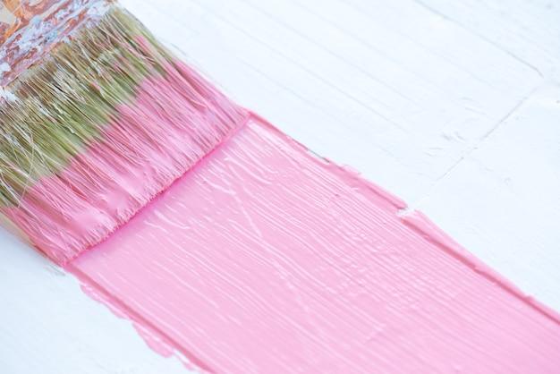 Feche acima do pincel que pinta a cor cor-de-rosa em uma tabela de madeira branca.