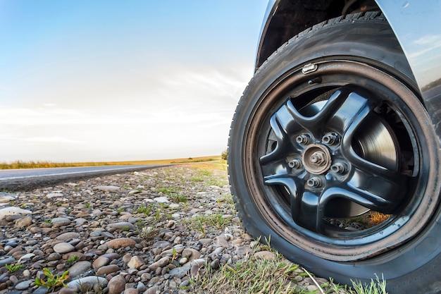 Feche acima do pneu furado em um carro na estrada de cascalho.