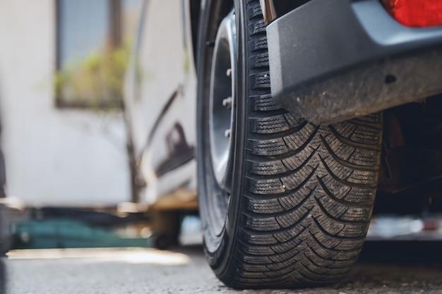 Feche acima do pneu novo ajustado no carro na oficina mecânica.