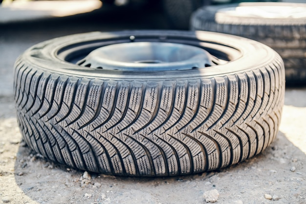 Feche acima do pneu velho na terra na oficina do auto mecânico.