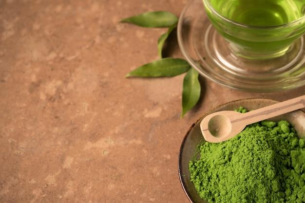 Feche acima do pó do chá verde com o copo de vidro do chá quente na tabela.