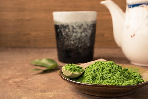 Feche acima do pó do chá verde no prato na tabela com fundo cerâmico do copo e do bule.