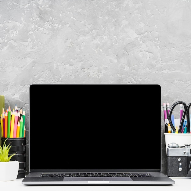 Feche acima do portátil da vista dianteira com fontes de mesa