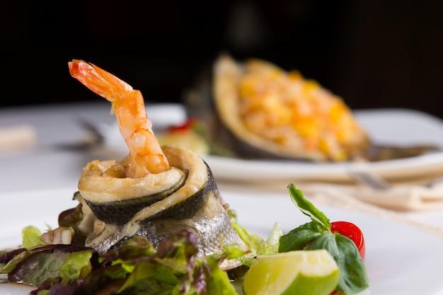 Feche acima do prato de frutos do mar ricos em proteínas saborosas de peixe e camarão em legumes com folhas e limão.