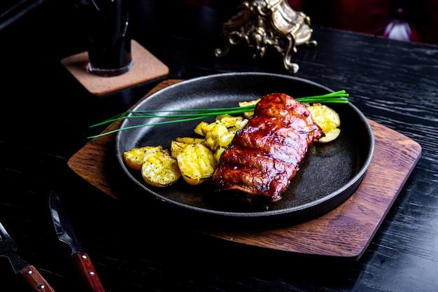Feche acima do prato principal gourmet com costela de porco grelhado e batatas fritas na panela preta. servido na placa de madeira