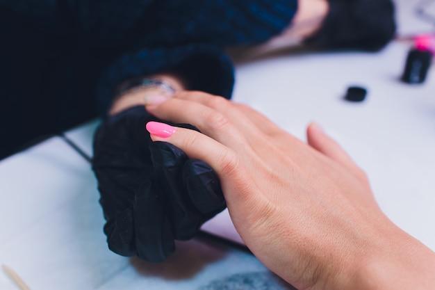 Feche acima do processo france manicure no salão de beleza.