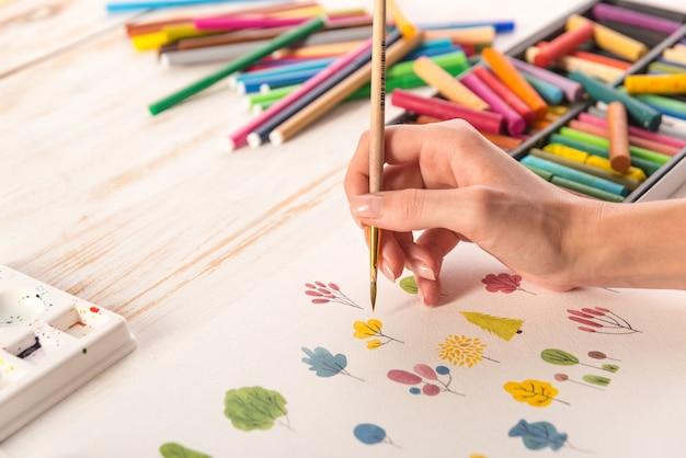 Feche acima do projeto colorido diferente da natureza das flores pintado com pincel e aquarelas no papel