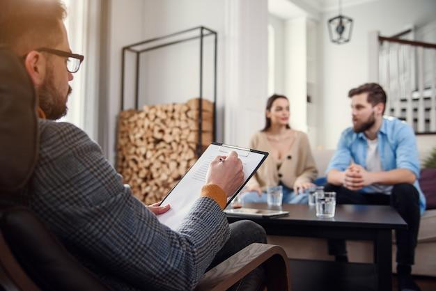 Feche acima do psicólogo masculino senta-se na cadeira e ouve casal jovem deprimido no escritório acolhedor elegante. foco seletivo.