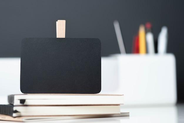 Feche acima do quadro negro no caderno com caixa de lápis moderno borrão