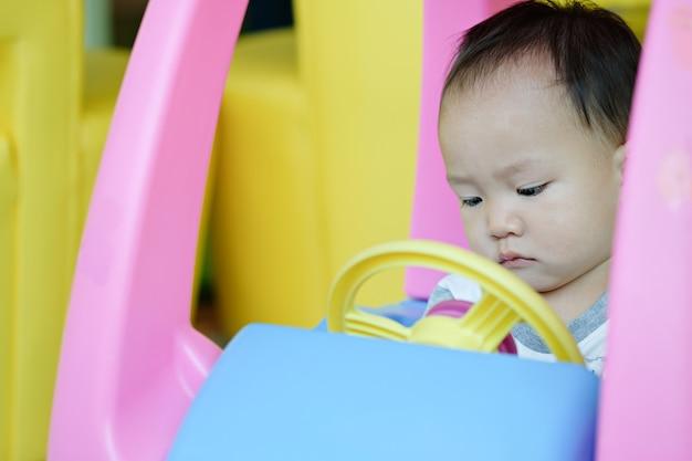 Feche acima do rapaz pequeno que conduz no carro plástico com espaço da cópia.